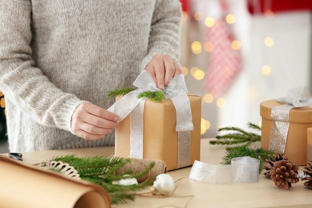 Cadeau d'emballage de femme pour noël à table