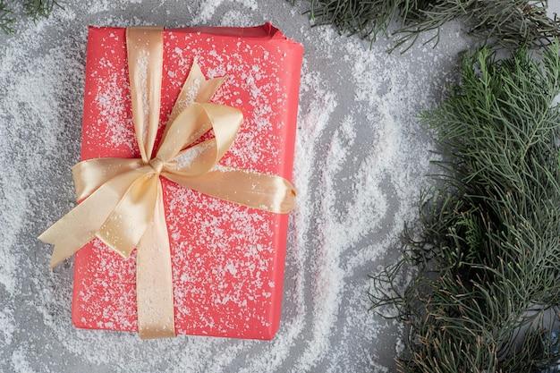 Cadeau avec emballage de ruban d'or assis sur de la poudre de noix de coco au milieu de branches de pin sur la surface en marbre