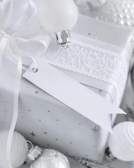 Cadeau emballé avec un arc blanc et une étiquette-cadeau en papier sur une table blanche avec des décorations de noël blanches et argentées se bouchent. composition d'hiver avec carte d'étiquette vierge, maquette, espace de copie