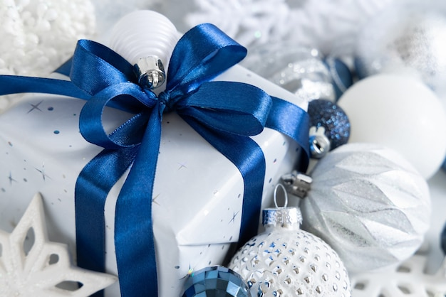 Cadeau emballé avec un arc bleu et des décorations de noël blanches, bleues et argentées autour de gros plan. composition hivernale
