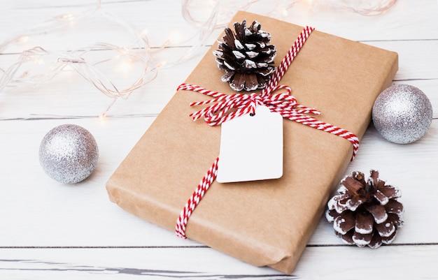 Cadeau emballé avec une corde rayée près des décorations de noël