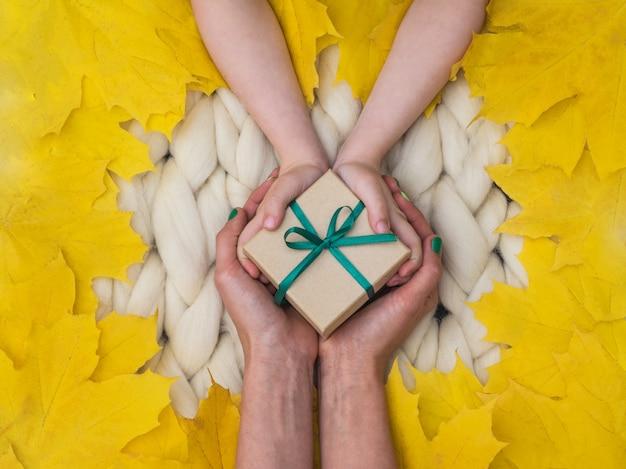 Cadeau emballé sur une couverture en laine mérinos, ambiance chaleureuse et confortable. fond en tricot.