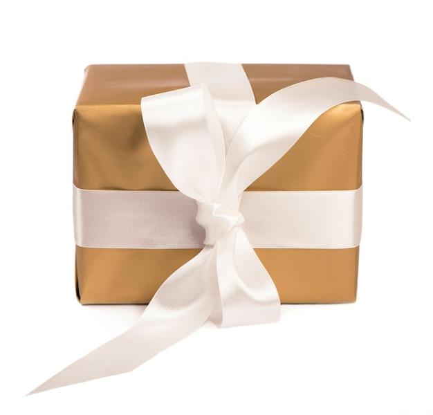 Cadeau emballé dans une boîte dorée avec ruban blanc isolé
