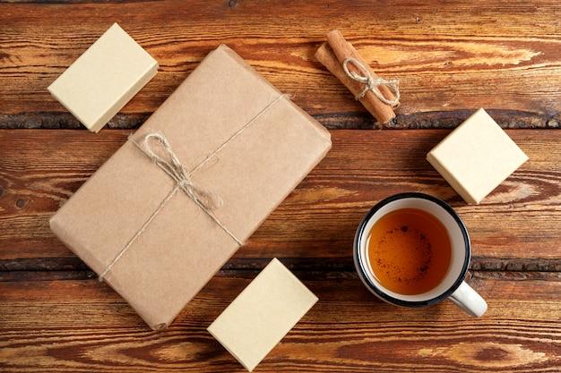 Cadeau emballé dans un carton biodégradable écologique et un verre de thé sur un fond en bois ancien foncé avec un espace vide pour le texte