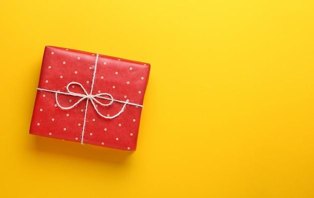 Un cadeau emballé dans du papier craft rouge à pois sur fond jaune.