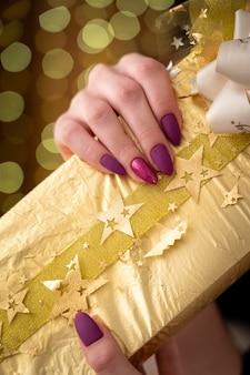 Cadeau emballé dans du papier doré bandé par un ruban décoré d'un nœud en tissu