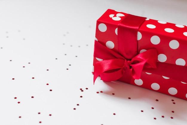 Cadeau emballé dans du papier rouge avec des cercles blancs et un noeud en satin rouge dessus se trouve sur un fond blanc avec des confettis.