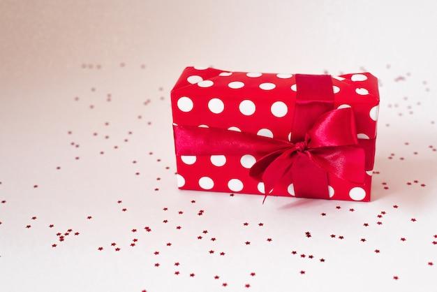 Un cadeau emballé dans du papier rouge avec des cercles blancs et un nœud en satin rouge