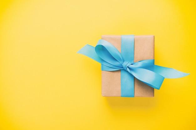 Cadeau emballé et décoré d'un arc bleu sur jaune avec l'espace de copie vintage, tonique. lay plat, vue de dessus