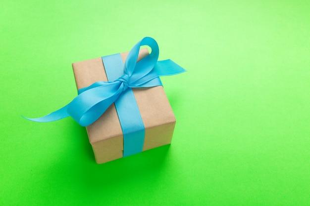 Cadeau emballé et décoré d'un arc bleu sur vert avec espace de copie. lay plat, vue de dessus