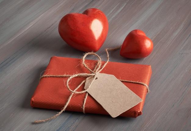Cadeau emballé avec une étiquette en papier vierge et deux cœurs en pierre rouge