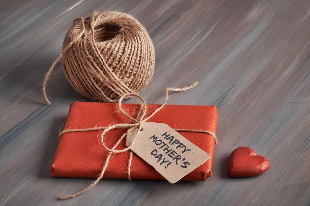 Cadeau emballé ligoté avec cordon, étiquette en carton avec texte
