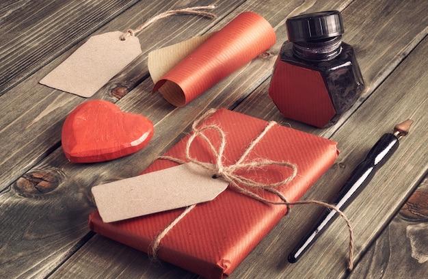 Cadeau emballé, papier d'emballage, étiquettes, puits d'encre, stylos et cœur décoratif sur bois