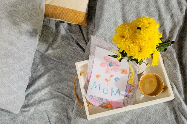 Un cadeau d'un enfant pour la fête des mères une carte d'une photo et un café au lit le matin