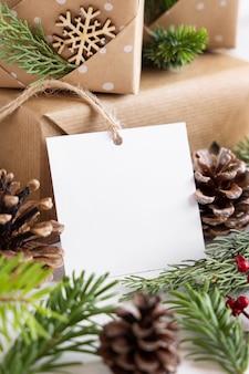 Cadeau enveloppé de noël avec une étiquette-cadeau en papier carré sur une table blanche avec des branches de sapin et des décorations en gros plan. composition d'hiver rustique avec maquette d'étiquette-cadeau vierge, espace de copie