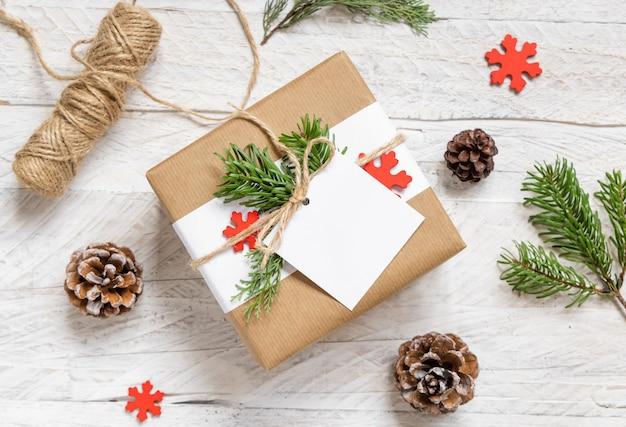 Cadeau enveloppé de noël avec une étiquette-cadeau en papier carré sur une table blanche avec des branches de sapin et des décorations vue de dessus. composition d'hiver rustique avec maquette d'étiquette-cadeau vierge, espace de copie