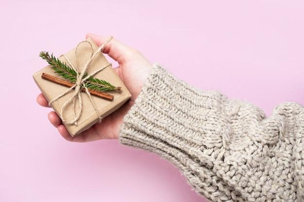 Cadeau fait de papier kraft et d'une branche d'arbre de noël dans les mains des femmes sur fond rose, gros plan. concept de cadeaux faits à la main. tendance moderne, emballage cadeau naturel de vos propres mains.