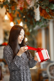 Cadeau femme en rouge tenant une boîte blanche. beau modèle mixte caucasien / asiatique isolé. la saint-valentin.