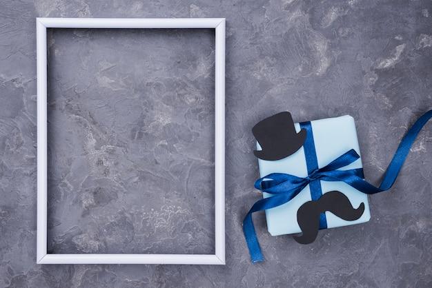 Cadeau de fête des pères avec rubans et cadre vide