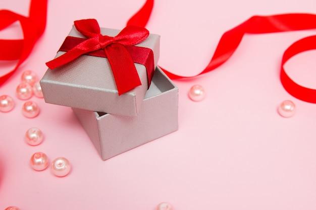 Cadeau sur fond rose avec des perles et un ruban rouge