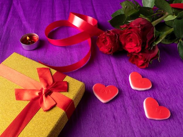 Cadeau jaune à côté de coeurs et ruban et roses rouges sur violet