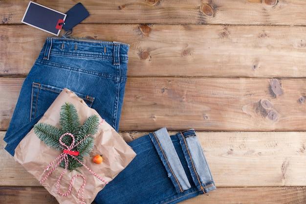 Cadeau, des jeans et des branches d'épicéa sur un bois brun