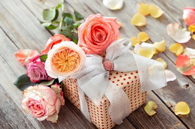 Cadeau joliment emballé et un bouquet de roses sur un fond en bois flou.