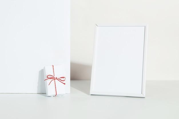 Cadeau kraft avec un ruban rouge et un cadre photo sur fond blanc