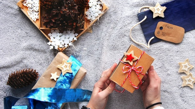 Cadeau en main. processus d'emballage cadeau. arc bleu. cadeaux en papier kraft. ambiance festive.