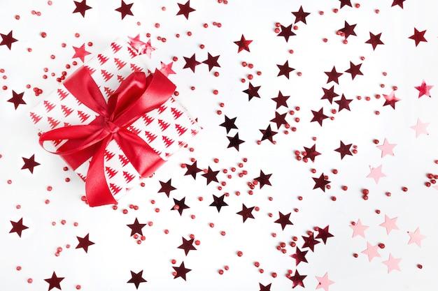 Cadeau de noël avec un arc rouge sur fond blanc avec des étoiles rouges et scintille. noël. content. nouvel an. style à plat