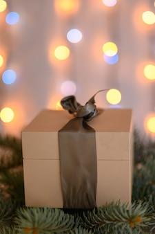 Un cadeau de noël avec un arc se trouve sur une branche d'arbre de noël dans le contexte d'une guirlande étincelante.