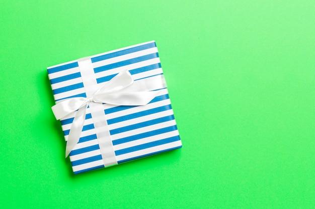 Cadeau de noël ou autre cadeau fait à la main emballé dans du papier avec un ruban blanc sur vert.