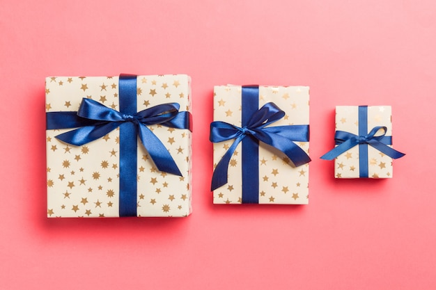 Cadeau de noël ou autre cadeau fait à la main emballé dans du papier avec un ruban bleu. coffret cadeau, décoration de cadeau sur table colorée, vue de dessus