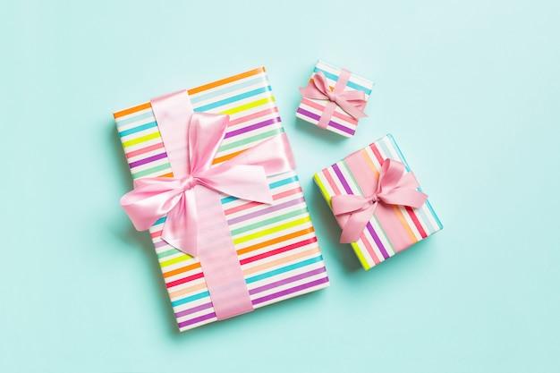 Cadeau de noël ou autre cadeau fait à la main emballé dans du papier avec un ruban rose sur fond bleu