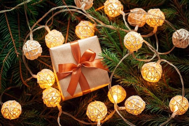 Cadeau de noël ou boîte cadeau sur fond de branches de sapin avec guirlande lumineuse