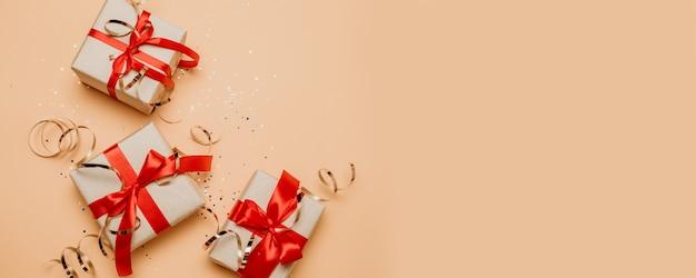 Cadeau de noël ou une boîte cadeau avec un noeud de ruban rouge et des décorations dorées sur fond pastel.