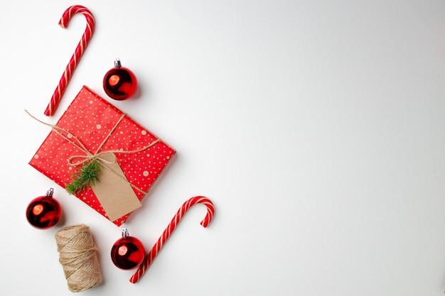Cadeau de noël avec des cannes de bonbon et des boules sur fond blanc