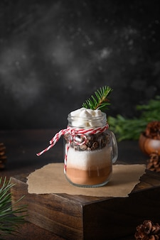 Cadeau de noël comestible fait maison en pot mason pour boisson au chocolat sur fond sombre. fermer. gâteries festives de noël. format vertical.