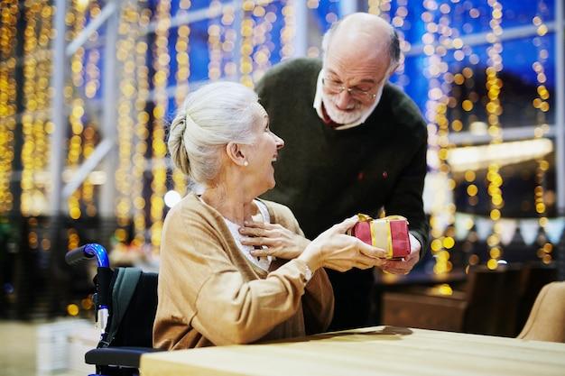 Cadeau de noël comme surprise pour femme, heureux couple de personnes âgées
