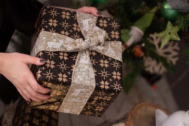 Un cadeau de noël dans un emballage marron avec un motif de flocons de neige avec un arc dans les mains féminines