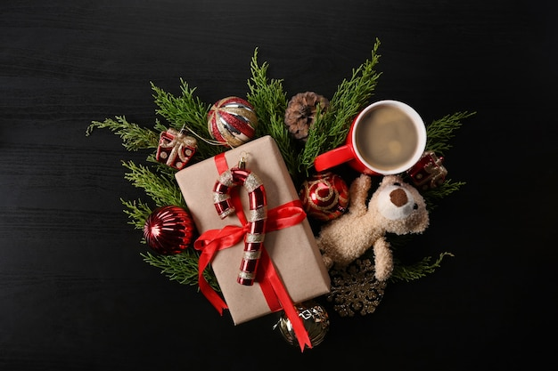 Cadeau de noël, décorations de noël et branches de sapin sur fond noir.