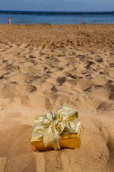 Un cadeau de noël doré sur la plage
