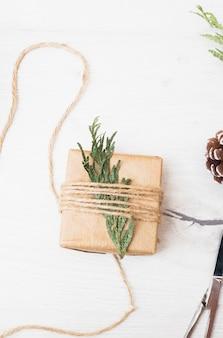 Cadeau de noël emballé avec une branche de sapin
