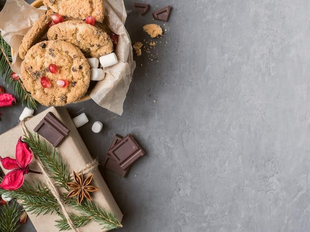 Cadeau de noël emballé dans du papier et une assiette de biscuits béton au chocolat, espace de copie