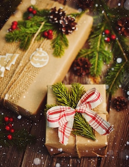 Cadeau de noël emballé dans du papier kraft avec décoration sur un fond en bois rustique d'en haut.
