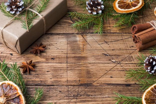 Cadeau de noël emballé avec des décorations sur une table en bois. espace de copie.