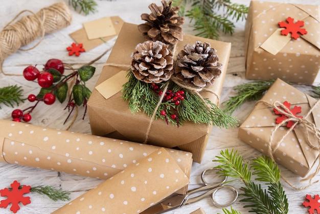Cadeau de noël emballé décoré de pommes de pin et de branches de genévrier