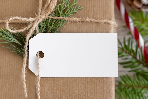 Cadeau de noël emballé avec une étiquette-cadeau en papier avec des branches de sapin, des pommes de pin et des décorations de vacances en gros plan. composition d'hiver rustique avec maquette d'étiquette-cadeau vierge, espace de copie, mise à plat