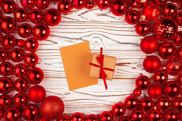 Cadeau de noël entouré de boules brillantes rouges