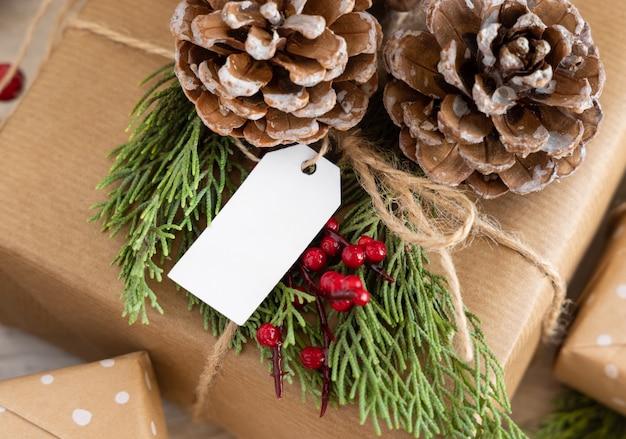 Cadeau de noël avec étiquette-cadeau vierge se bouchent, maquette
